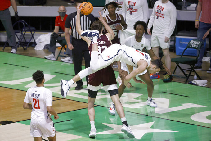 Mississippi State forward Quinten Post (32) looks to shoot as Richmond forward Tyler Burton (3) tumbles over behind him as Richmond guard Isaiah Wilson (21) watches during the first half of an NCAA college basketball game in the semifinals of the NIT, Thursday, March 25, 2021, in Denton, Texas. (AP Photo/Ron Jenkins)
