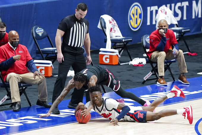 South Carolina's T.J. Moss, top, and Mississippi's Jarkel Joiner, bottom, dive for the ball in the first half of an NCAA college basketball game in the Southeastern Conference Tournament Thursday, March 11, 2021, in Nashville, Tenn. (AP Photo/Mark Humphrey)