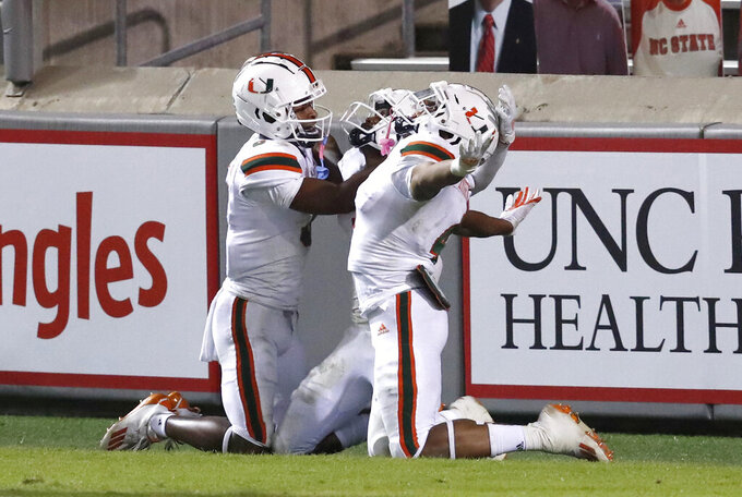 Miami's Mark Pope, left and Jaylan Knighton, right, celebrate with Mike Harley, rear, after Harley scored on 54-yard touchdown during the second half of Miami's 44-41 victory over North Carolina State in an NCAA college football game Friday, Nov. 6, 2020, in Raleigh, N.C. (Ethan Hyman/The News & Observer via AP, Pool)