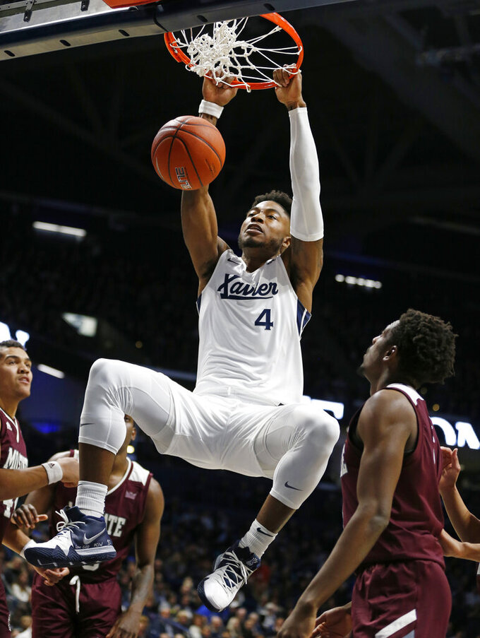 Xavier forward Tyrique Jones (4) dunks over Missouri State guard Keandre Cook, right, during the first half of an NCAA college basketball game, Friday, Nov. 15, 2019, in Cincinnati. (AP Photo/Gary Landers)