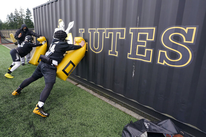 Pacific Lutheran players take part in a blocking drill against a storage container during football practice Tuesday, Feb. 2, 2021, in Tacoma, Wash. For all the attention heaped on the FBS level of college football last fall as it tried to play, it will not be the only college football during the 2020-21 sports calendar as a handful of NCAA Division III and NAIA programs begin some form of a winter/spring season Saturday, Feb. 6. (AP Photo/Ted S. Warren)