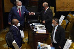 Republican Reps. John O. Read of Gautier, second from left, and Tom Weathersby of Florence, second from right, fist bump while Democratic colleagues Carl Mickens of Brooksville, left, and Charles Young Jr., of Meridian, right, confer during the first day of the 2021 Mississippi Legislature, Jan. 5, 2021, in Jackson, Miss. Many legislators are changing some of the ways they conduct business because of newly diagnosed coronavirus cases at the Capitol with a goal of constantly wearing face masks and putting more space between people in a building where crowded rooms can be the norm. (AP Photo/Rogelio V. Solis)