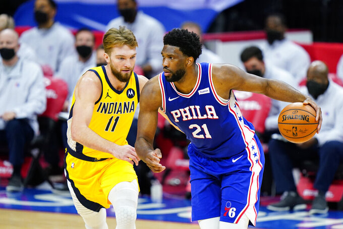 Philadelphia 76ers' Joel Embiid (21) dribbles against Indiana Pacers' Domantas Sabonis (11) during the first half of an NBA basketball game, Monday, March 1, 2021, in Philadelphia. (AP Photo/Matt Slocum)