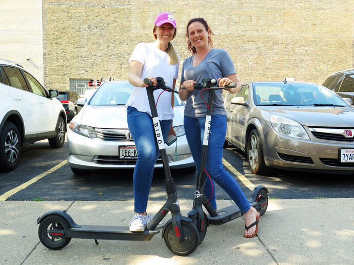 In this Wednesday, July11, 2018 photo, Kirby Bridges, left, and Megan Garlington pose with the Bird scooters they were taking for an afternoon ride in Milwaukee. Milwaukee is suing California-based Bird to stop the company from renting bikes because the city contends they are illegal to operate on streets and sidewalks. (AP Photo/Ivan Moreno)