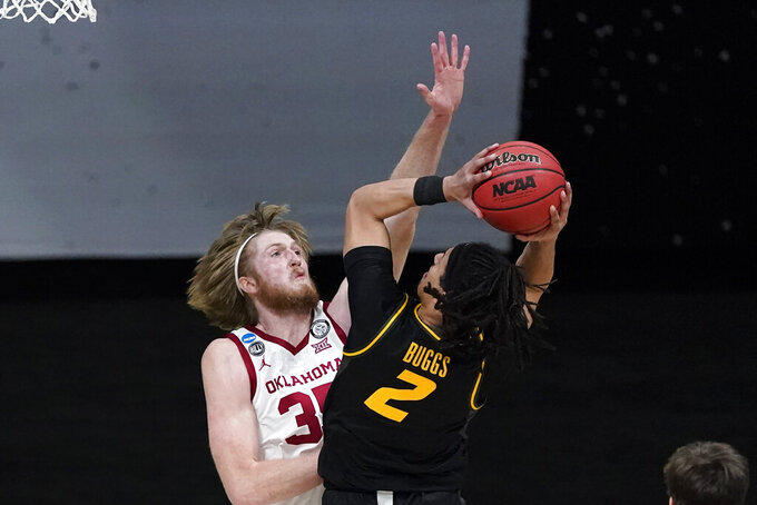 Missouri guard Drew Buggs (2) shoots over Oklahoma forward Brady Manek, left, during the first half of a first-round game in the NCAA men's college basketball tournament at Lucas Oil Stadium, Saturday, March 20, 2021, in Indianapolis. (AP Photo/Darron Cummings)