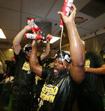 Oakland Athletics' Fernando Rodney is doused in the clubhouse celebration after clinching a wild card spot after the baseball game against the Seattle Mariners, Monday, Sept. 24, 2018, in Seattle. (AP Photo/John Froschauer)