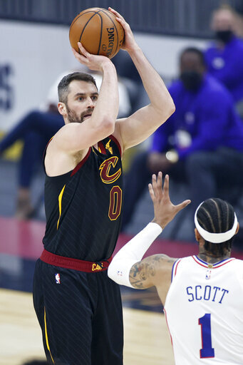 Cleveland Cavaliers' Kevin Love (0) shoots over Philadelphia 76ers' Mike Scott (1) in the first half of an NBA basketball game, Thursday, April 1, 2021, in Cleveland. (AP Photo/Ron Schwane)