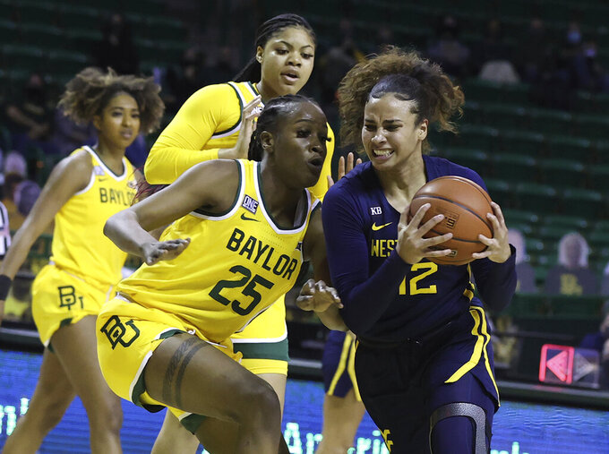 West Virginia forward Esmery Martinez, right, drives on Baylor center Queen Egbo in the first half of an NCAA college basketball game, Monday, March 8, 2021, in Waco, Texas. (Rod Aydelotte/Waco Tribune-Herald via AP)