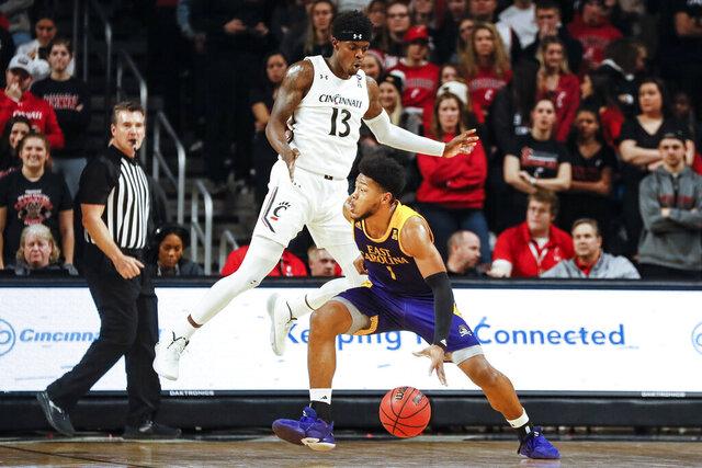 East Carolina's Jayden Gardner (1) looks to pass around Cincinnati's Tre Scott (13) during the first half of an NCAA college basketball game, Sunday, Jan. 19, 2020, in Cincinnati. (AP Photo/John Minchillo)