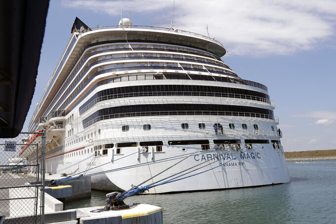 FILE -In this Saturday, April 4, 2020, file photo, Carnival cruise line ship Carnival Magic is docked at Port Canaveral, in Cape Canaveral, Fla. Carnival Corp. says it lost $2 billion in the first quarter as the cruise industry remained shut down in many parts of the world by the pandemic. But the company says bookings are picking up, and 2022 could be a strong year for cruises. (AP Photo/John Raoux, File)