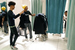 Jadon Cofield, left, and Houston Texans' De'Andre Hopkins, center, comment on an outfit modeled by Miracle Washington-Tribble, right, in a fitting area at H&M during a shopping spree Monday, Dec. 16, 2019, at Galleria Mall in Houston. The two teens are beneficiaries of Eight Million Stories, a Houston program which helps 14-18-year-olds who have either quit or been kicked out of school continue their education, find employment and receive emotional support. (AP Photo/Michael Wyke)