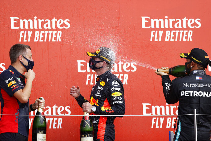 Mercedes driver Lewis Hamilton of Britain, right, sprays champagne on Red Bull driver Max Verstappen of the Netherlands who the 70th Anniversary Formula One Grand Prix at the Silverstone circuit, Silverstone, England, Sunday, Aug. 9, 2020. (Andrew Boyers, Pool via AP)