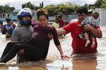FILE - In this Nov. 5, 2020 file photo, a pregnant woman is carried out of an area flooded by water brought by Hurricane Eta in Planeta, Honduras. Thousands of homes were damaged and the infamous gang violence has not relented in Honduras, where some residents said gangs were charging a tax to boats trying to rescue people from flooded neighborhoods. (AP Photo/Delmer Martinez, File)