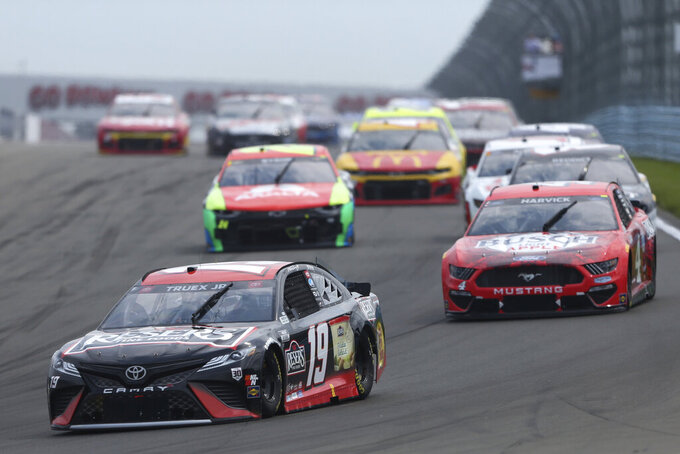 Martin Truex Jr. leads a group of cars as he rounds Turn 1 during a NASCAR Cup Series auto race in Watkins Glen, N.Y., on Sunday, Aug. 8, 2021. (AP Photo/Joshua Bessex)