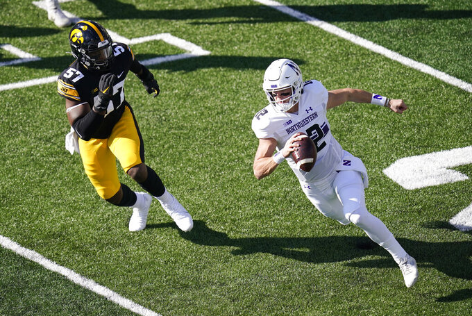 Northwestern quarterback Peyton Ramsey runs from Iowa defensive lineman Chauncey Golston (57) during the first half of an NCAA college football game, Saturday, Oct. 31, 2020, in Iowa City, Iowa. (AP Photo/Charlie Neibergall)