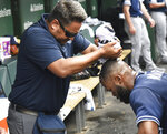 San Diego Padres' trainer Michael Salazar, left, uses a wet towel to cool off San Diego Padres' Manuel Margot (7) during the second inning of a baseball game against the Chicago Cubs, Friday, July,19, 2019, in Chicago. (AP Photo/David Banks)