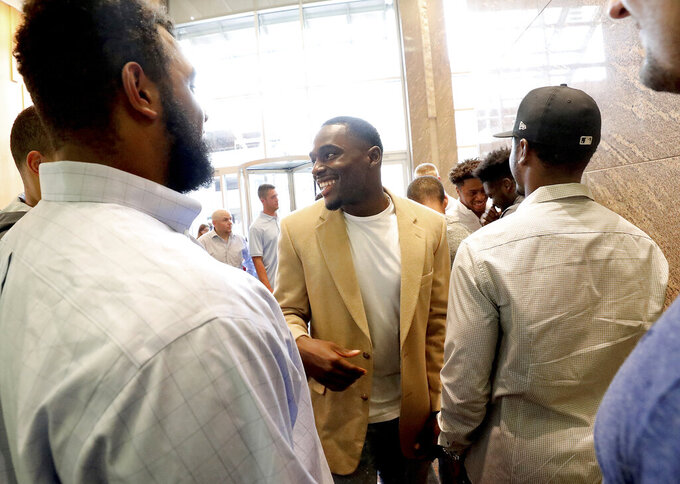Former Wisconsin Badger football player Quintez Cephus, center, greets current members of the team following a press conference to reiterated his request for reinstatement to the university in Madison, Wis. Monday, Aug. 12, 2019. The former wide receiver was acquitted earlier this month of sexual assault charges stemming from a campus incident in his apartment. He was expelled from the university in March after the university's own internal investigation. (John Hart/Wisconsin State Journal via AP)