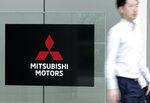 A man walks past a sign of Mitsubishi Motors at its headquarter in Tokyo Friday, June 21, 2019. Mitsubishi Motors Corp. shareholders approved on Friday the ouster of Carlos Ghosn, who was pivotal in the Japanese automaker's three-way partnership with Nissan and Renault until he was arrested on financial misconduct charges last year. (AP Photo/Eugene Hoshiko)