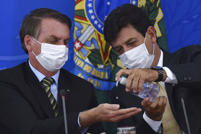 FILE - In this March 18, 2019 file photo, Brazil's Health Minister Luiz Henrique Mandetta, right, gives anti-bacterial gel to President Jair Bolsonaro as they give a press conference on the new coronavirus at Planalto presidential palace in Brasilia, Brazil. Mandetta criticized Bolsonaro's dismissive handling of the COVID-19 pandemic on national television Sunday night, April 12, and the president's repeated threats to fire him are worrying health experts who say that amid governmental chaos, the health minister's advice to limit contact and take the virus seriously has played a major role in preventing Brazil's epidemic from being even worse.  (AP Photo/Andre Borges, File )