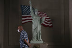 FILE - In this  June 22, 2020, file photo, a man with a face mask walks past a replica of Statue of Liberty in Los Angeles. (AP Photo/Jae C. Hong, File)