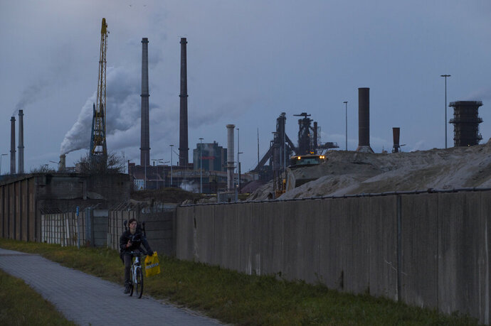 FILE - In this Dec. 4, 2018 file photo, a cyclist passes heavy industries in IJmuiden, Netherlands. In a statement Friday, June 28, 2019, the Dutch government presented a comprehensive raft of measures aimed at slashing the Netherlands' emission of carbon blamed for warming the Earth's atmosphere by 50% by 2030. (AP Photo/Peter Dejong, file)