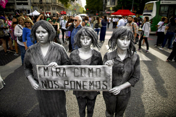 A trio of women hold a sign with a message that reads in Spanish: