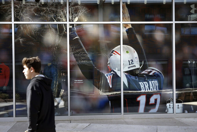 A passer-by walks past an oversized photograph of former New England Patriots football quarterback Tom Brady, Wednesday, March 18, 2020, at Patriot Place mall, in Foxborough, Mass. Brady said on social media on Tuesday, March 17, 2020 that he would not be returning to the Patriots and has become a free agent. (AP Photo/Steven Senne)