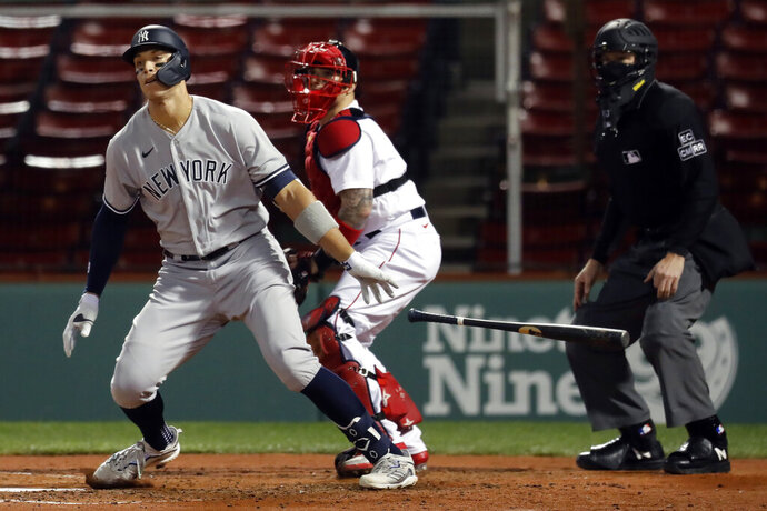New York Yankees' Aaron Judge, left, grounds into a double play in front of Boston Red Sox's Christian Vazquez during the third inning of a baseball game Friday, Sept. 18, 2020, in Boston. (AP Photo/Michael Dwyer)