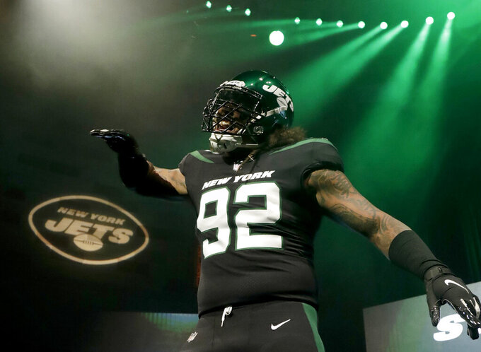 "New York Jets defensive end Leonard Williams models the NFL football team's new ""stealth black"" uniform Thursday, April 4, 2019, in New York. (AP Photo/Julio Cortez)"