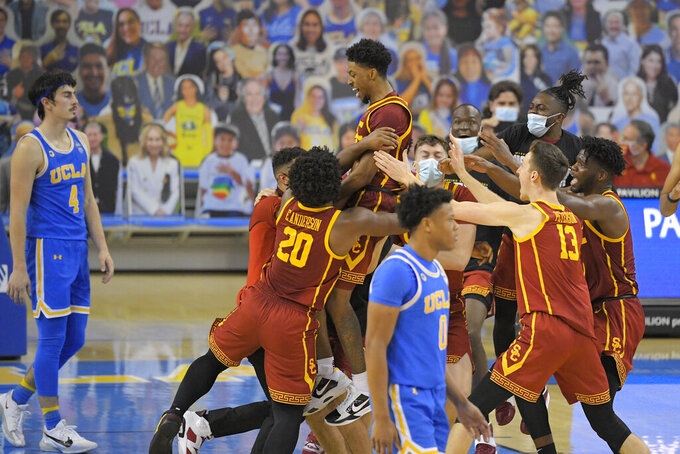 Southern California guard Tahj Eaddy, top, celebrates with teammates as UCLA guard Jaime Jaquez Jr., left, and guard Jaylen Clark walk off the court after Eaddy hit a game-winning three-point shot during the second half of an NCAA college basketball game Saturday, March 6, 2021, in Los Angeles. USC won 64-63. (AP Photo/Mark J. Terrill)