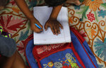 A child practices writing numbers on a sidewalk class in New Delhi, India, on Sept. 3, 2020. An Indian couple, Veena and her husband Virendra Gupta, is conducting free classes for underprivileged children on a sidewalk in New Delhi with the goal to keep them learning and not left behind when schools reopen. It all began when Veena's maid complained that with schools shut, children in her impoverished community were running amok and wasting time. As most schools in India remain shut since late March when the country imposed a nationwide lockdown to curb the spread of COVID-19, many switched to digital learning and taking classes online. (AP Photo/Manish Swarup)