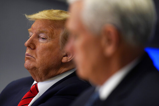 FILE - In this March 19, 2020, file photo President Donald Trump listens during a teleconference with governors at the Federal Emergency Management Agency headquarters in Washington. Vice President Mike Pence is at right. When President Donald Trump speaks, financial markets gyrate and quiver in real time. (AP Photo/Evan Vucci, Pool, File)