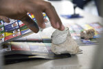 Rocks are used as paperweights to keep ballots from flying away while electoral officials count votes after polls closed during the presidential elections, in Santo Domingo, Dominican Republic, Sunday, July 5, 2020. (AP Photo/Tatiana Fernandez)