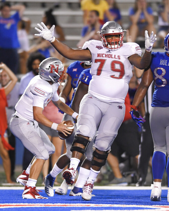 FILE - In this Sept. 1, 2018, file photo, Nicholls State quarterback Chase Fourcade, left, celebrates his touchdown in overtime against Kansas with offensive lineman P.J. Burkhalter (79), during an NCAA college football game, in Lawrence, Kan. Burkhalter was selected to The Associated Press FCS All-America first team, Tuesday, Dec. 17, 2019.  (AP Photo/Reed Hoffmann)
