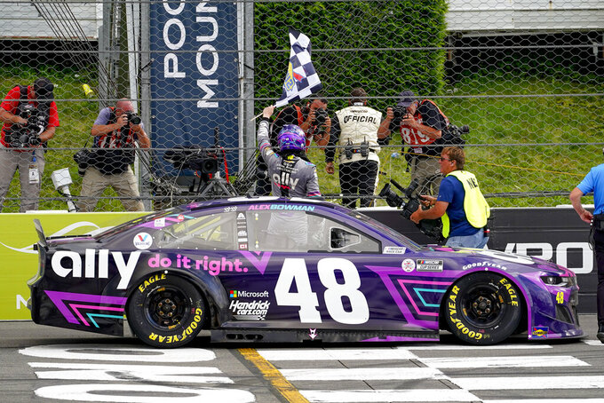 Alex Bowman driver of car 48, waves the checker flag in celebration of his win after passing Kyle Larson on the last lap of the NASCAR Cup Series auto race at Pocono Raceway, Saturday, June 26, 2021, in Long Pond, Pa. (AP Photo/Matt Slocum)