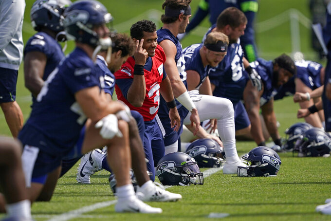 Seattle Seahawks quarterback Russell Wilson (3) smiles as he stretches before practice during NFL football training camp, Wednesday, Aug. 12, 2020, in Renton, Wash. (AP Photo/Ted S. Warren, Pool)