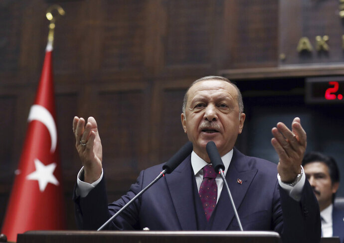 Turkish President Recep Tayyip Erdogan addresses his ruling party legislators at the Parliament, in Ankara, Wednesday, Oct. 30, 2019. Erdogan said Turkey would not hesitate to relaunch its operation if the Syrian Kurdish fighters do not fully evacuate the 30 kilometer (19 mile) area in northeastern Syria or continue attacks against Turkish troops. (AP Photo/Burhan Ozbilici)