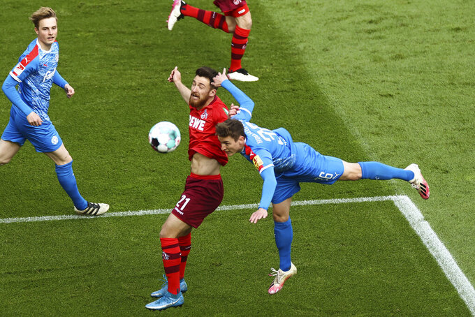 Cologne's Salih Ozcan, center, in a header duel with Kiel's Niklas Hauptmann during the Bundesliga relegation soccer match between FC Cologne and Holstein Kiel at the Rhein-Energie-Stadion in Cologne, Germany, Wednesday, May 25, 2021. (Rolf Vennenbernd/Pool photo via AP)