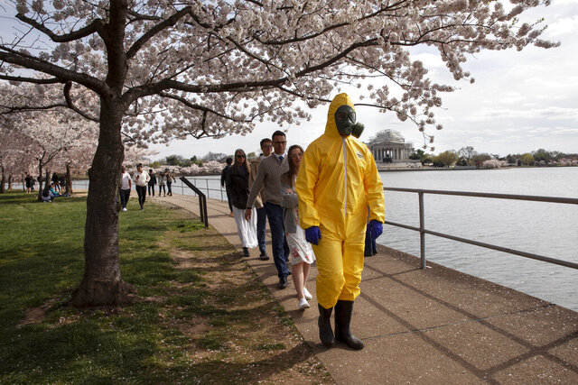 A 17-year-old who asked not to be named wears a yellow hazmat suit, gas mask, boots, and gloves as he walks with his family, from Gaithersburg, Md., under cherry blossom trees in full bloom along the tidal basin, Sunday, March 22, 2020, in Washington.