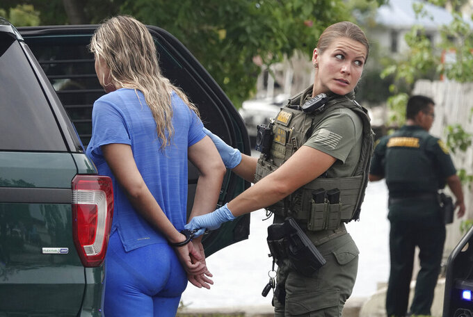 A Broward Sheriff's Office Deputy detains one of the migrants who came ashore on the intracoastal waterway Thursday, June 17, 2021, in Pompano Beach, Fla. (Joe Cavaretta/South Florida Sun-Sentinel via AP)