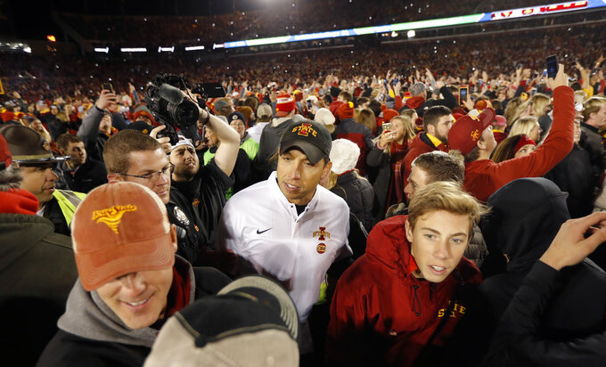 Iowa State head coach Matt Campbell, center, celebrates with fans on the field after an NCAA college football game against West Virginia, Saturday, Oct. 13, 2018, in Ames, Iowa. (AP Photo/Charlie Neibergall)