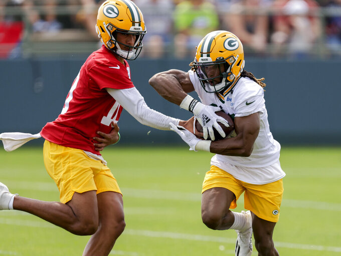 Green Bay Packers' quarterback Jordan Love hands the ball off to running back Aaron Jones during NFL football training camp Wednesday, July 28, 2021, in Green Bay, Wis. (AP Photo/Matt Ludtke)