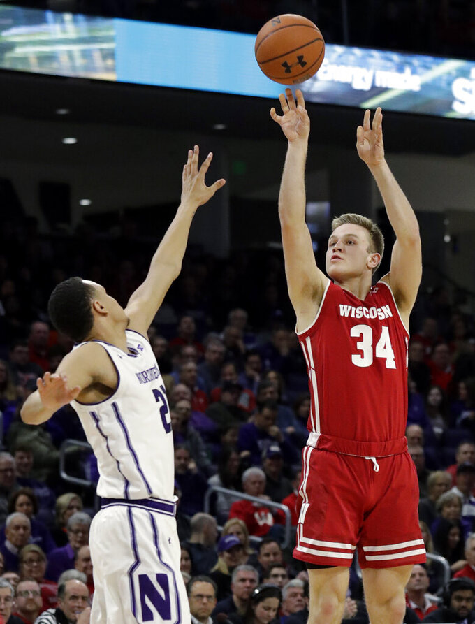 Wisconsin guard Brad Davison, right, shoots against Northwestern forward A.J. Turner during the first half of an NCAA college basketball game Saturday, Feb. 23, 2019, in Evanston, Ill. (AP Photo/Nam Y. Huh)