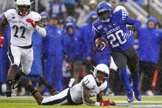 Kentucky running back Kavosiey Smoke (20) runs the ball during the first half of the NCAA college football game against Louisville, Saturday, Nov. 30, 2019, in Lexington, Ky. (AP Photo/Bryan Woolston)