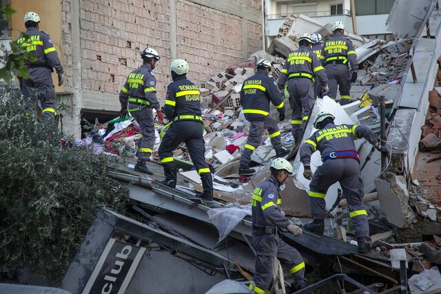 In this photo taken on Wednesday, Nov. 27, 2019, rescuers from Romania operate at a collapsed building after the 6.4-magnitude earthquake in Durres, western Albania. In the initial hours after a deadly pre-dawn earthquake struck Albania, pancaking buildings and trapping dozens of sleeping people beneath the rubble, the country's neighbors sprang into action. Offers of help flooded in from across Europe and beyond, with even traditional foes setting aside their differences in the face of the natural disaster. The 6.4-magnitude earthquake that struck Albania on Tuesday killed at least 49 people, injured 2,000 and left at least 4,000 homeless. (AP Photo/Visar Kryeziu)