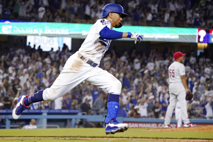 Los Angeles Dodgers' Mookie Betts rounds first after hitting a solo home run as Philadelphia Phillies relief pitcher Ranger Suarez stands on the mound during the seventh inning of a baseball game Tuesday, June 15, 2021, in Los Angeles. (AP Photo/Mark J. Terrill)