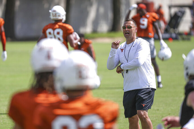 FILE - In this Aug. 7, 2021, file photo, Texas coach Steve Sarkisian watches players run drills during an NCAA college football practice in Austin, Texas. Texas gave Sarkisian, a former head coach at Washington and Southern California, a guaranteed six-year, $34 million contract that should take him into the eventual move to the SEC planned for 2025, if it doesn't happen sooner. (Aaron E. Martinez/Austin American-Statesman via AP, File)