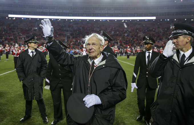 University of Wisconsin-Madison Marching Band Director Mike Leckrone waves to the fans in the stadium after an NCAA college football game Saturday, Nov. 24, 2018, in Madison, Wis. Leckrone is retiring after 50 years of directing the UW band. Minnesota beat Wisconsin 37-15. (AP Photo/Andy Manis)