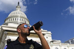 A Capitol Hill police officer takes a drink as he stands his post on the West side of Capitol Hill in Washington, Saturday, July 20, 2019. The National Weather Service said