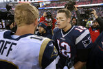 FILE- In this Dec. 4, 2016, file photo, New England Patriots quarterback Tom Brady right, speak at midfield to Los Angeles Rams quarterback Jared Goff after the Patriots won 26-10 in an NFL football game in Foxborough, Mass. The wide-eyed, talented Goff will try to lead his Rams past the grizzled, 41-year-old Brady, who is looking to guide the Patriots to their sixth Super Bowl victory.  (AP Photo/Steven Senne, File)